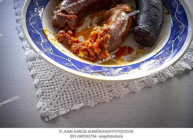 Red chorizo and black sausage morcilla just boiled on a plate over knitting cloth. Closeup