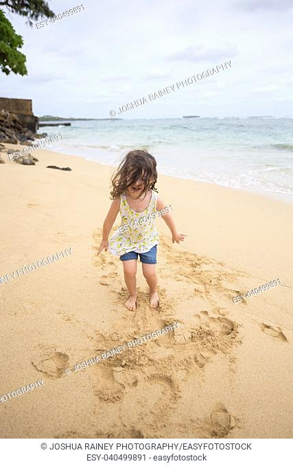 Lifestyle portrait of a young three year old girl playing on the beach in Oahu Hawaii