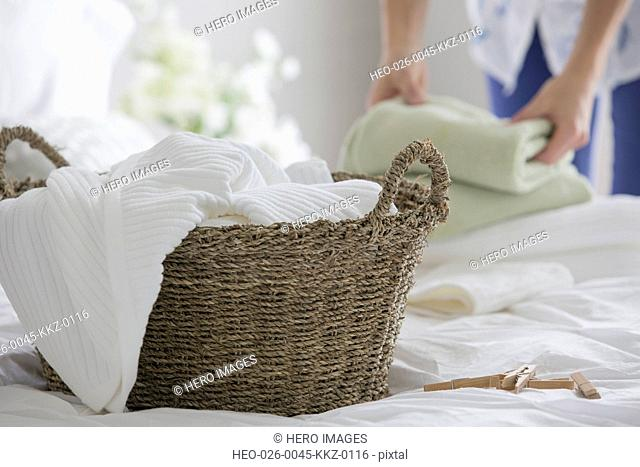 Woman folding clean laundry in bedroom