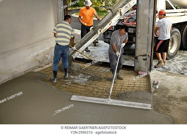 Work crew pouring cement from a cement truck shute over wire mesh on a residential garage floor and spreading with large float trowel and rake Toronto Ontario...
