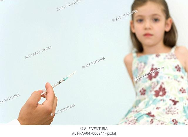 Doctor holding syringe, preparing to vaccinate little girl, cropped