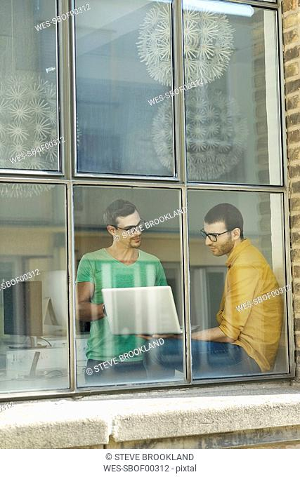 Young professionals at the window using laptop