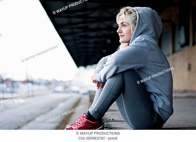 Portrait of mid adult female runner in grey hoody, sitting gazing