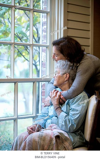 Woman hugging mother in wheelchair near window