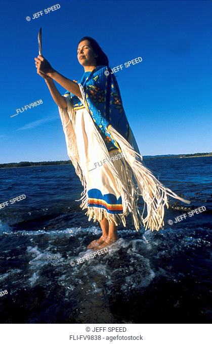 Anishnawbe Woman standing on Rock in Water, Manitoulin Island, Ontario
