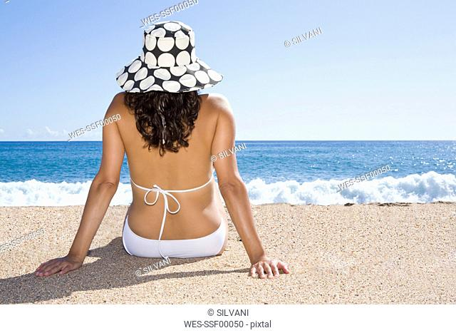France, Corsica, Woman relaxing on beach, rear view