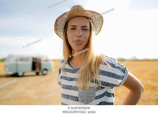 Portrait of young woman at camper van in rural landscape sticking out her tongue