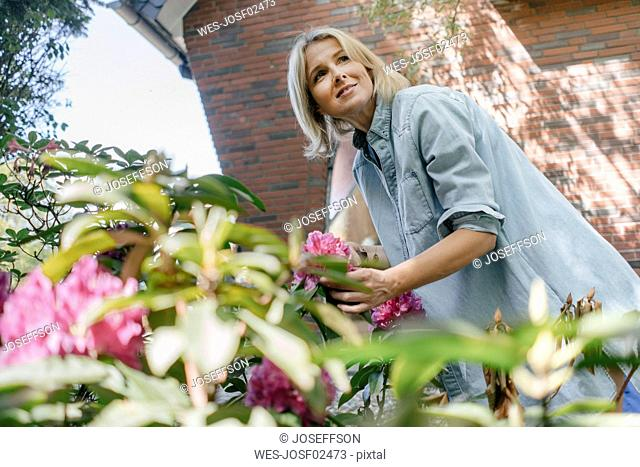 Smiling mature woman with flowers in garden