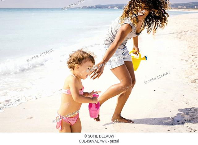 Mother and toddler daughter with toy watering cans on beach, Tuscany, Italy