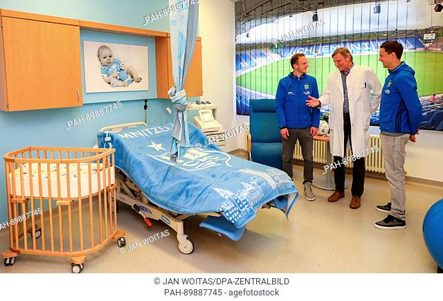 Lutz Kaltofen (M), chief physician for gynaecology explains the new football themed delivery room in the colours of FC Chemintz to Chemnitz' players Julius...