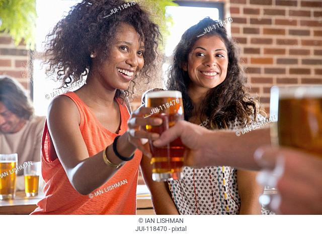Barman Serving Female Customers Pints Of Beer In Bar