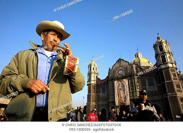A musician plays a flute and a drum outside the Our Lady of Guadalupe Basilica in Mexico City, December 11, 2007  Millions of Mexican pilgrims converged on the...