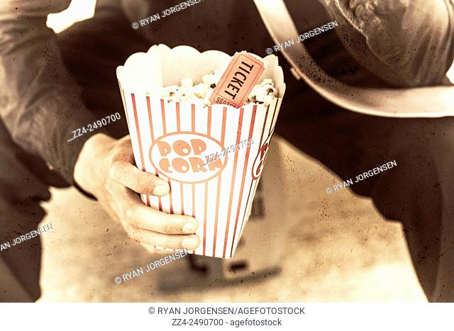 Vintage style poster of an old retro popcorn box with movie tickets. Movie snack food