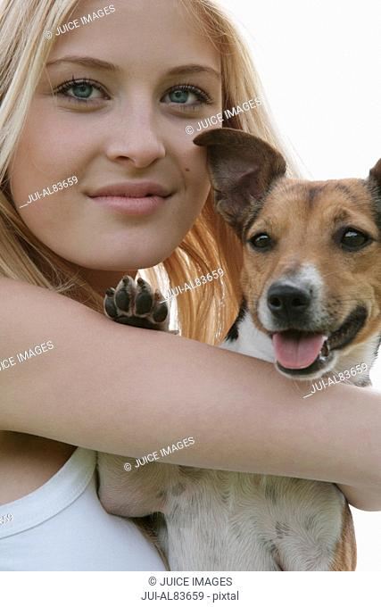 Young woman holding small dog outdoors