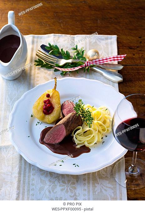 Plate of venison filet with ribbon noodles, stuffed pear and red wine sauce
