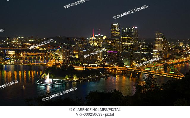 (Time-lapse/Zoom-in) Night falls on the downtown area of Pittsburgh, Pennsylvania including the skyline, bridges, and Point State Park at the confluence of the...