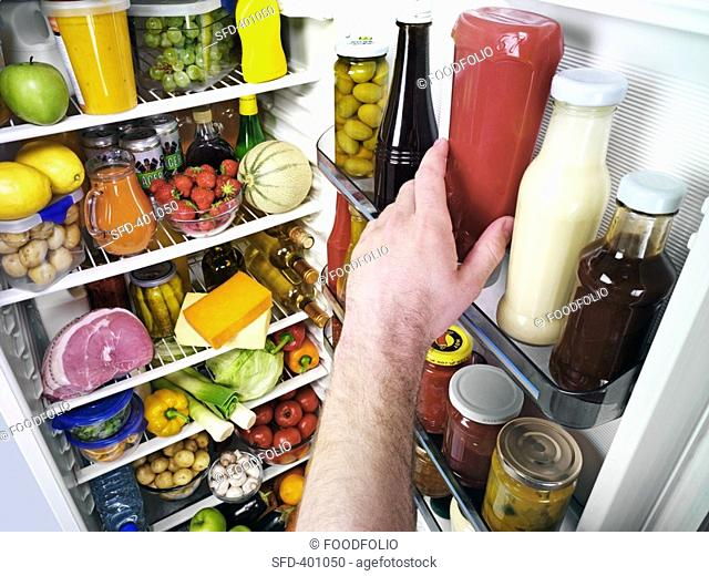 Hand reaching for ketchup bottle in a refrigerator Not available for exclusive usages