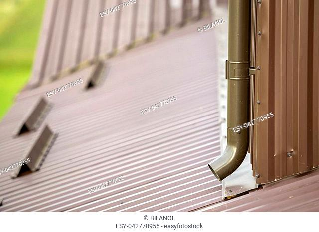 Close-up of brown new gutter metal system pipe on blurred copy space background. Vertical construction for draining rain water from building roof on the wall