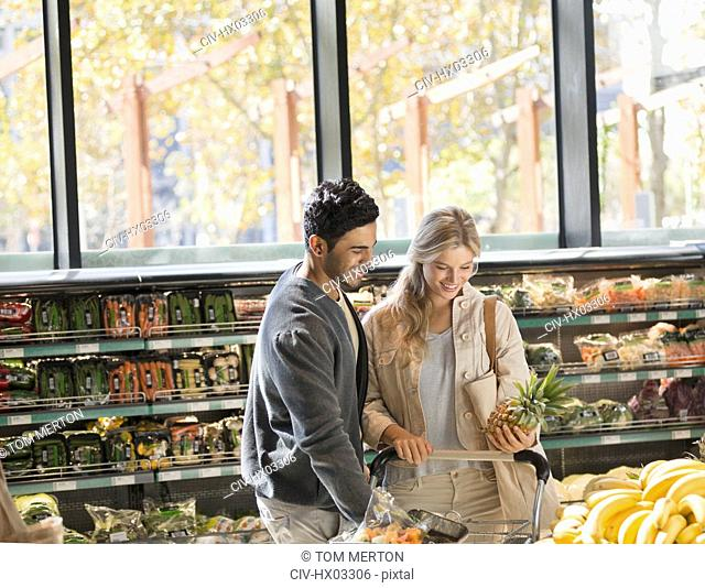 Smiling young couple grocery shopping, holding pineapple in market