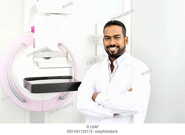 Portrait of confident male doctor standing arms crossed by mammography machine in hospital