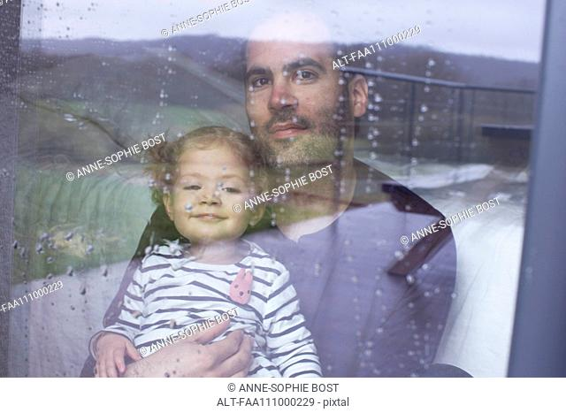 Man with young child looking through window watching rain fall