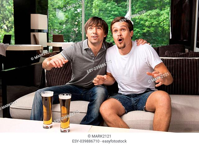 Two male football fans cheering football team. Drinking bear in pub, green trees on background