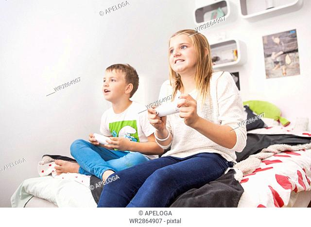 Low angle view of siblings playing video game at home
