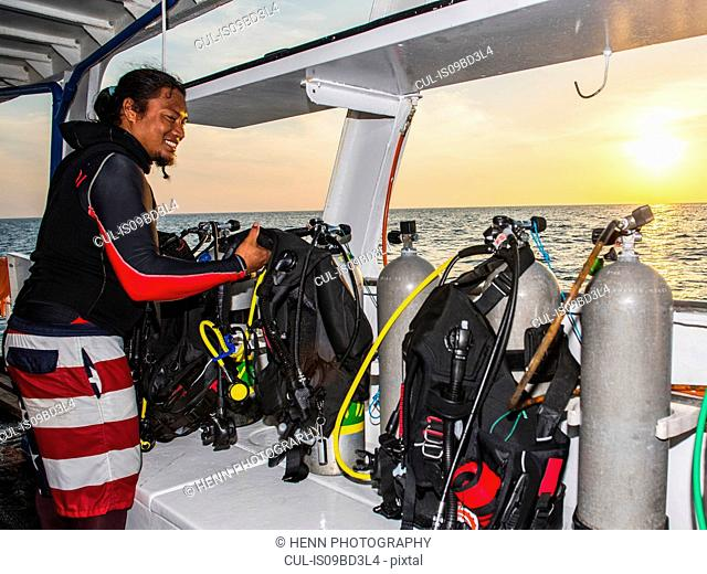 Man checking dive gear on board dive boat, Tubbataha Reefs Natural Park, Sulu Sea, Philippines