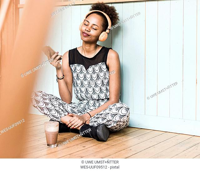 Smiling young woman sitting on floor listening to music