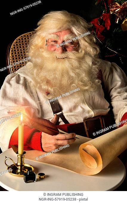 Santa Claus sitting at home and writing on old paper roll to do list with quill pen and ink at night with candle light. Authentic vintage style portrait