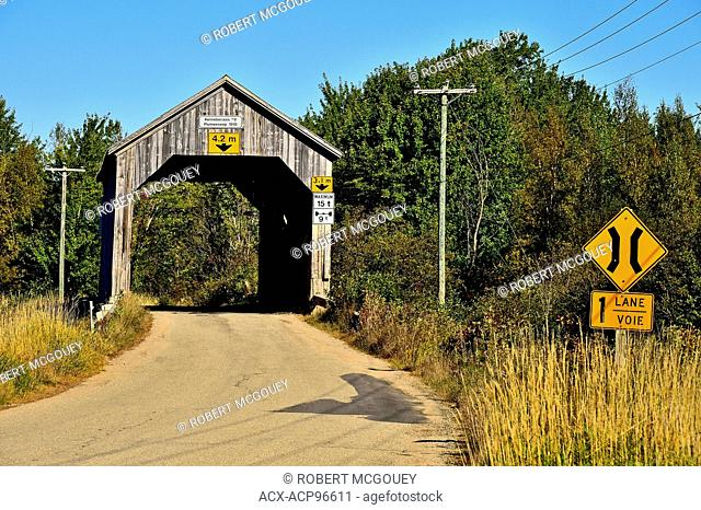A wooden single lane covered bridge built in 1910, spanning a stream on a two lane road at Plumweseep in rural New Brunswick, Canada