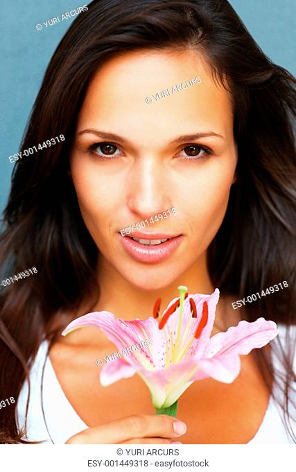 Head shot of pretty woman holding a flower looking directly in camera