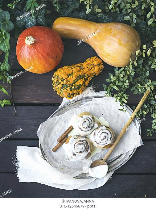 Cinnamon pumpkin buns with creamy cheese icing and ripe pumpkins over a dark wood background