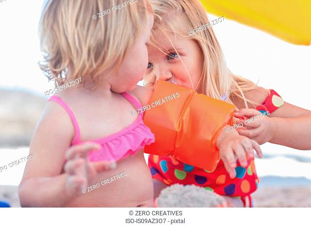 Girl inflating toddler sister's inflatable armband on beach, Cape Town, South Africa
