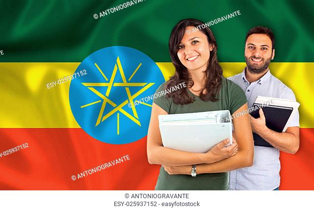 Couple of young students with books over Ethiopian flag