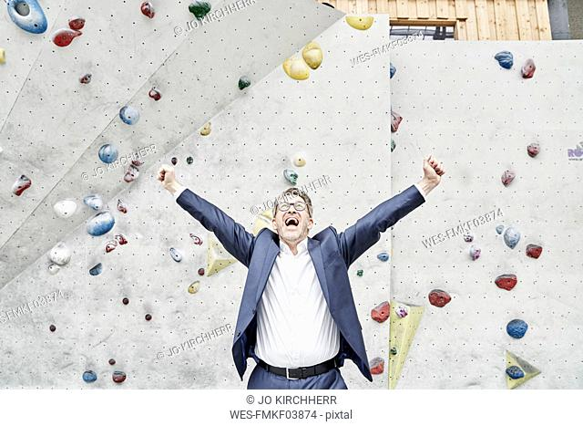Successful businessman in a bouldering hall