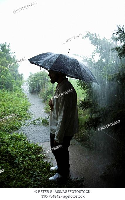 Young man, holding an umbrella, standing in a rainstorm