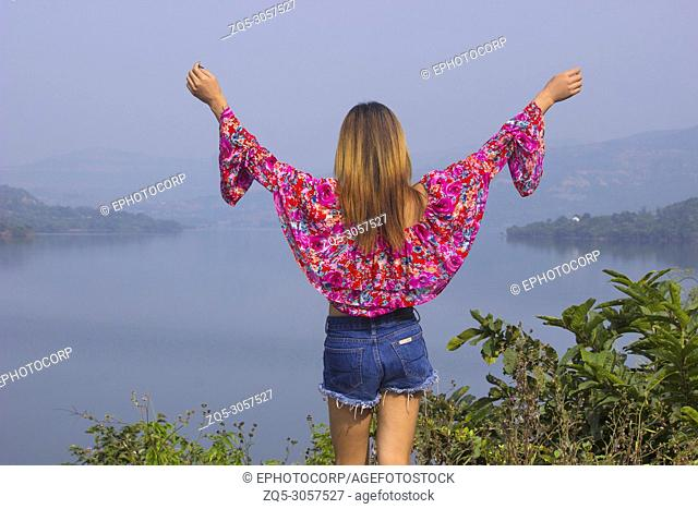 Back view of woman with floral top and denim shorts with raised hands looking at a lake