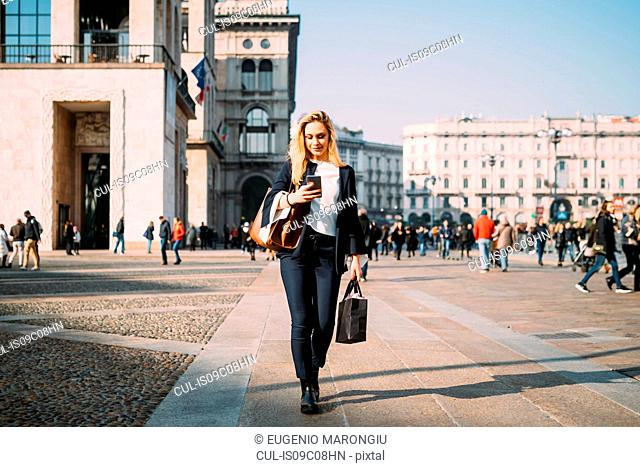 Young female tourist with shopping bags strolling and looking at smartphone in city square, Milan, Italy