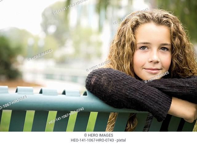 Thoughtful girl relaxing on park bench
