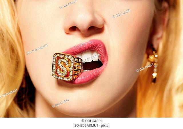 Close up of young woman with diamond ring in her mouth