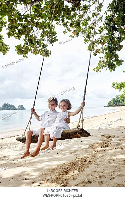 Thailand, Ko Yao Noi, happy boy and little girl on a swing on the beach