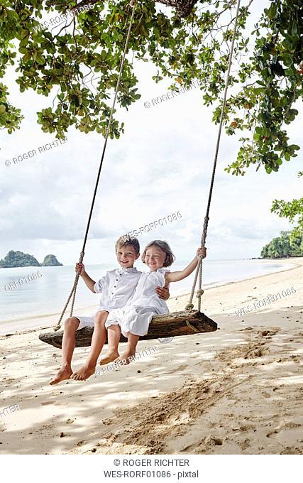 Thailand, Ko Yao Noi, happy boy and little girl on a swing on the beach