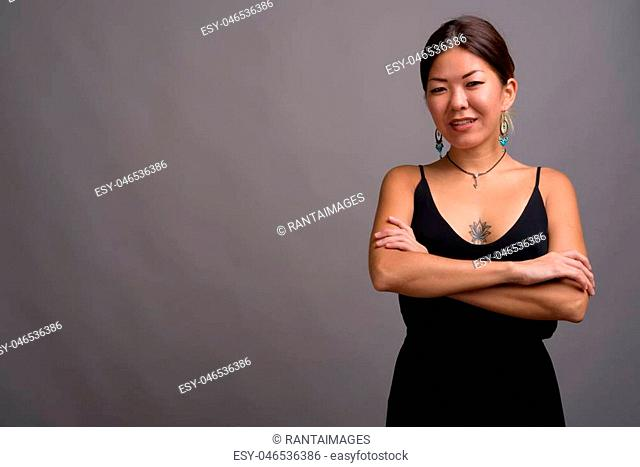 Studio shot of young beautiful Kazakh woman wearing formal black dress against gray background