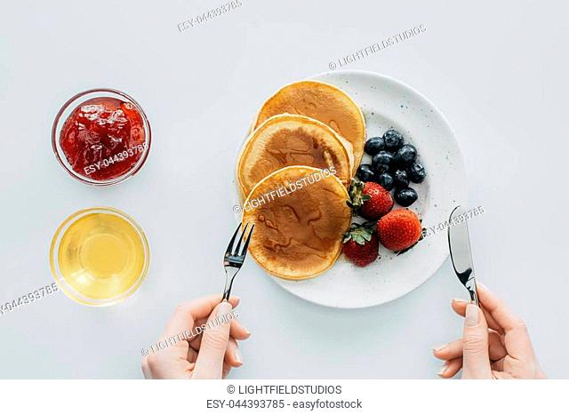 cropped shot of woman eating pancakes with berries on white table