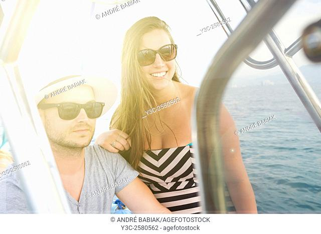 Young man and young woman enjoying a boat ride on vacation