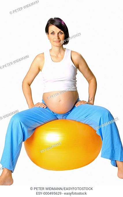 A pregnant woman does exercises with a stability ball