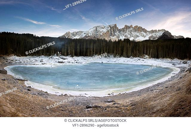a panoramic view of the whole Karersee during the winter season with the latemar Gruppe in the background