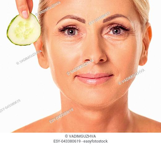 Portrait of beautiful middle aged woman with bare shoulders looking at camera and smiling, isolated on white, close-up. Slice of cucumber near her eyes