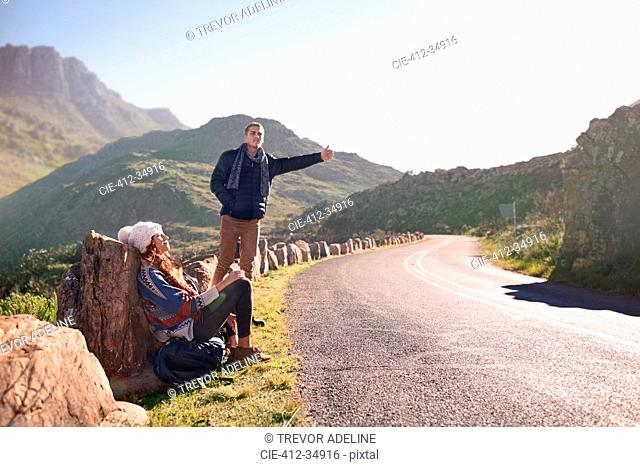 Young couple hitchhiking at sunny, remote roadside